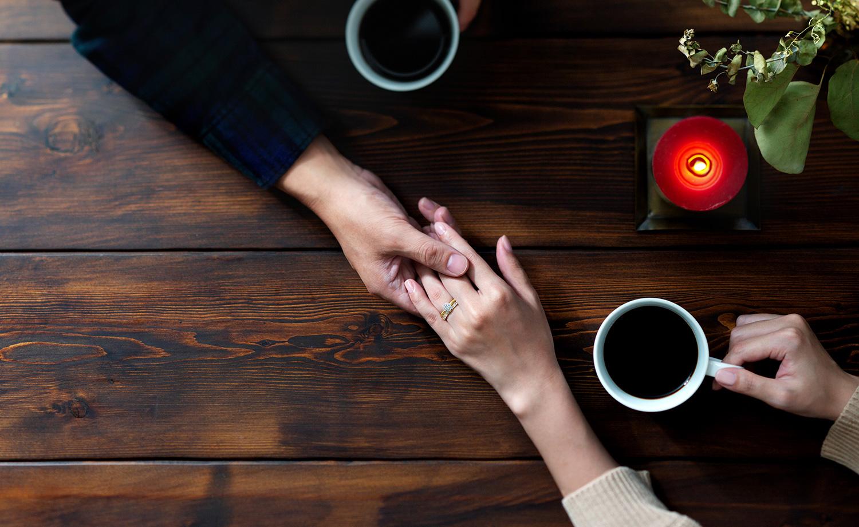 婚約指輪を装着した女性の手を握る男性