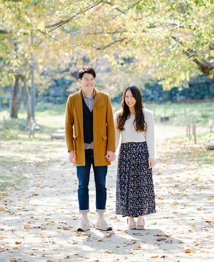 銀杏並木で手を繋ぐ夫婦