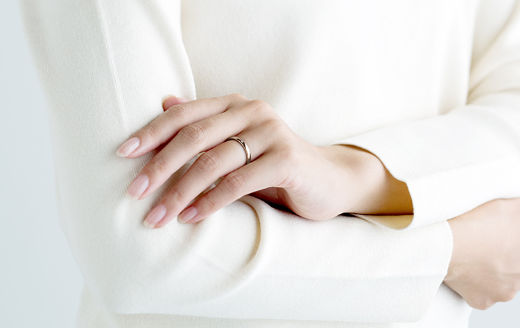 シャンパンゴールドの結婚指輪を装着した女性
