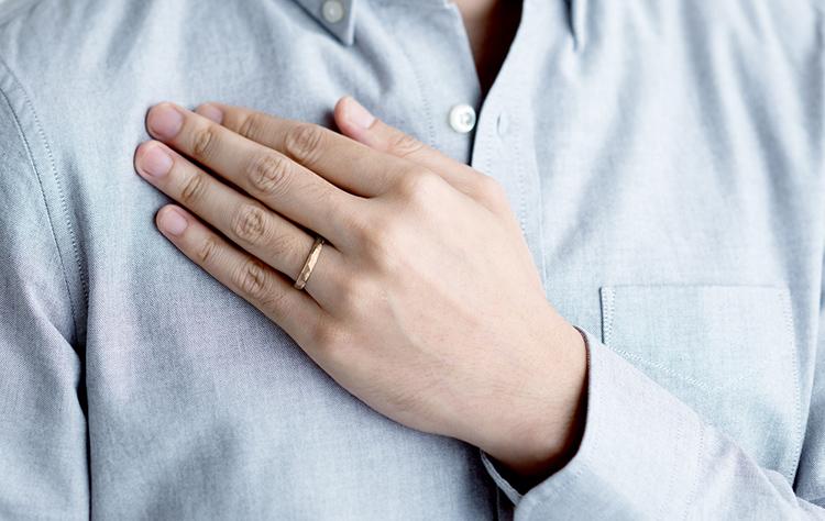 シャンパンゴールドの結婚指輪を装着した男性