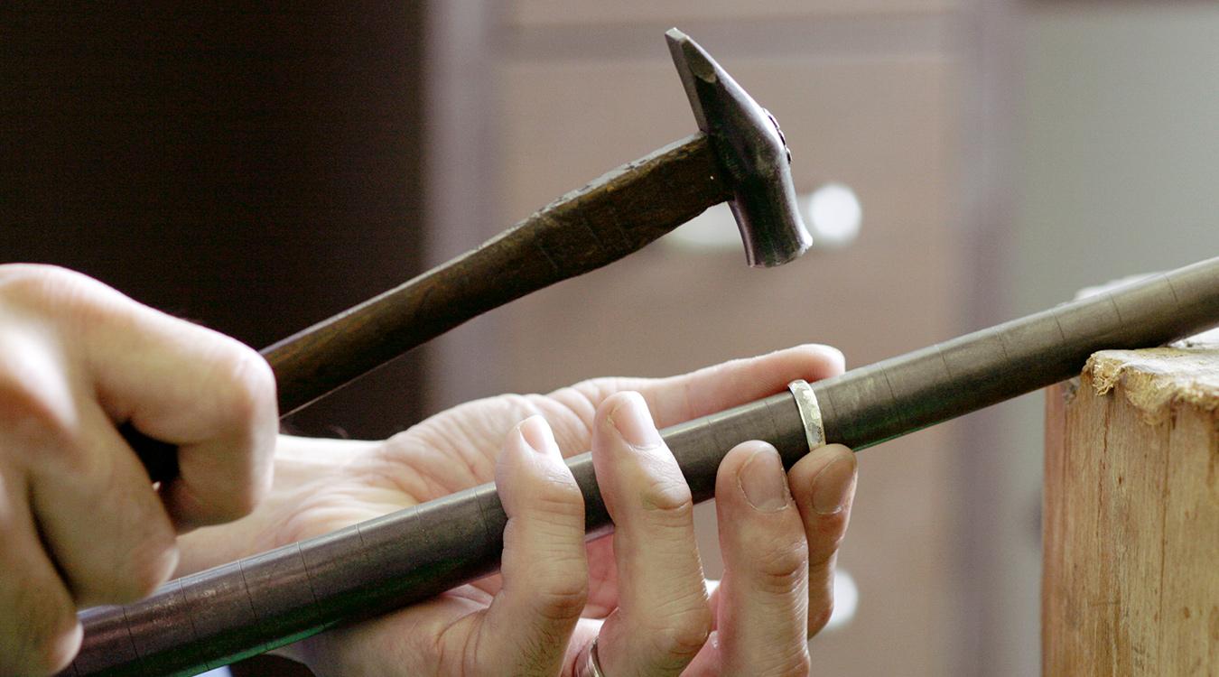 職人が小槌でひとつひとつの面を形作る結婚指輪