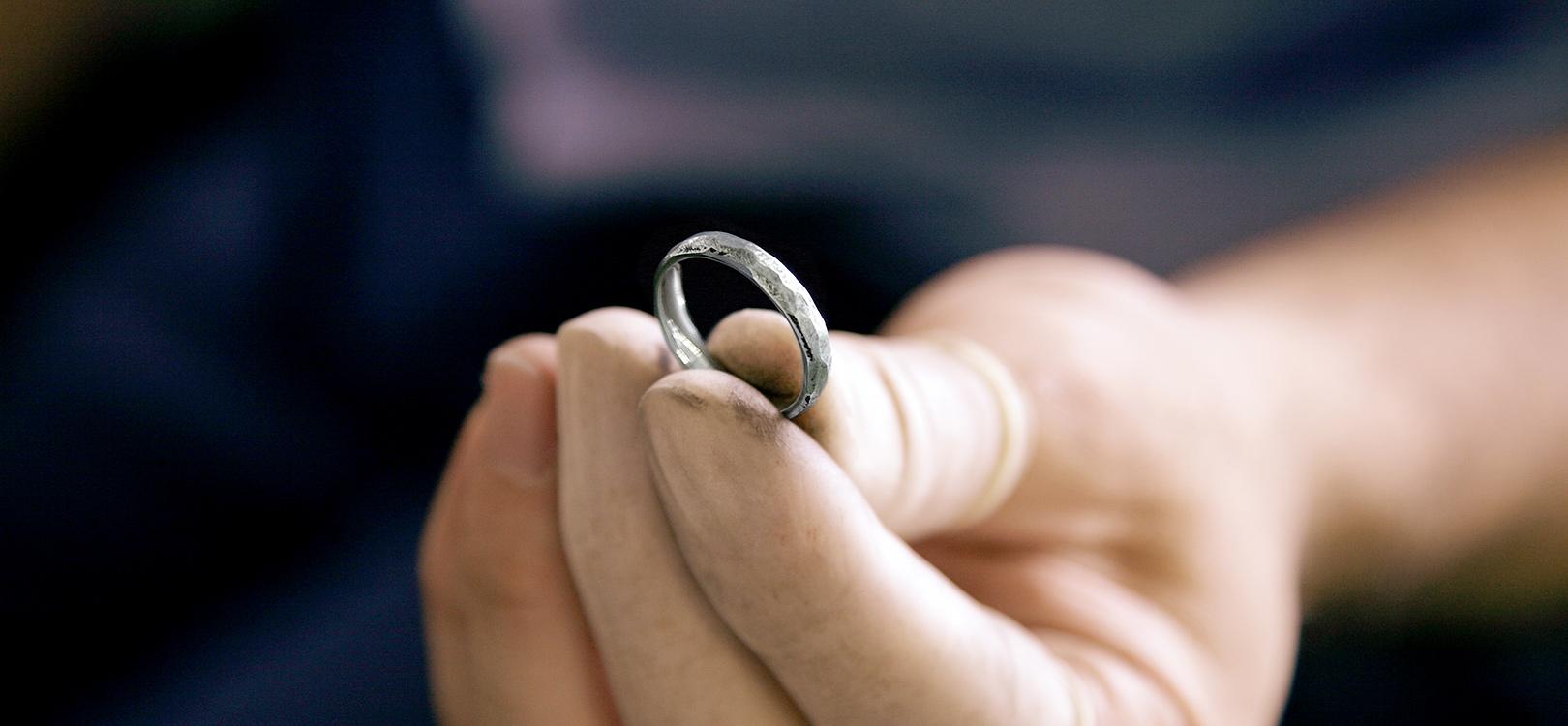 仕上げた結婚指輪を持っている職人の手元